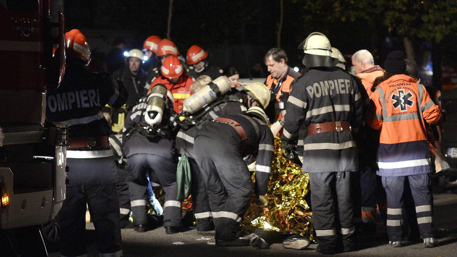 epa05004125 Romanian fireworkers and paramedics are trying to rescue a survivor of an explosion at a club, in Bucharest, Romania, early 31 October 2015. At least 26 people were killed and more than 60 were injured according to the first Interior Ministry report, in an accidental explosion, possibly triggered by mistakenly used fireworks, during a pop album launching concert.  EPA/STR